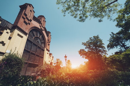 Wide angle view of beautiful park with varied vegetation, ancient building with grid and brick facade, bright sunny summer day with clean sky, Barcelona, Spain