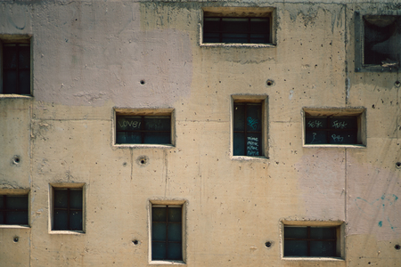 freaked: Close-up view of beige facade of residential house with irregular dark windows of different form and small circle holes , sunny summer day, Barcelona, Spain