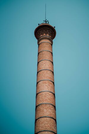 tall chimney: View from bottom of brick chimney with arrester on top and regular metal ties on body, clean teal sky behind, Barcelona, Spain Stock Photo