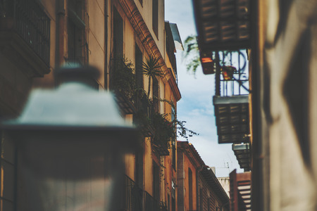 View of facades of residential houses on narrow street with sky behind with a lot of balconies, windows home plants, blurred lantern in front,  Barcelona historical district El Born, sunny summer day