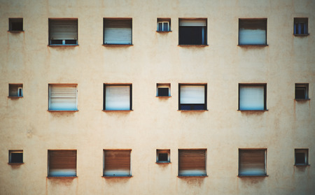 architectonics: Beige facade of residential building in Barcelona with regular pattern of windows of different size, streaks of rust under the sills