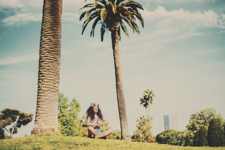 blessedness: Woman with slim body making yoga exercise, attractive young curly girl practicing yoga on meadow of green park with palms on hot sunny day with teal sky, young beautiful brunette making yoga outdoors