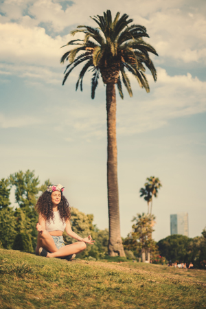 blessedness: Woman with curly hair making yoga exercise, attractive young girl with beautiful body practicing yoga in green park next to palm, young beautiful brunette making yoga outdoors Stock Photo