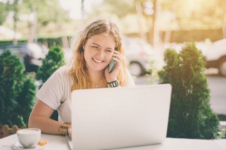 overweight students: Plus size girl talking with her family on smartphone and using laptop while sitting in street cafe with cup of coffee, smiling girl in white t-shirt having work conversation on her cellphone outdoors