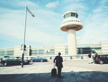 Rear view of businessman with luggage standing outside of airport in front of air traffic control tower and parking, experienced male employer with suitcase waiting for taxi outdoors after work travel