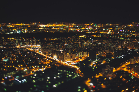 night shift: True tilt shift shooting of residential district of night metropolis from very high above: multiple residential houses and orange lights from windows, strong bokeh in background and foreground