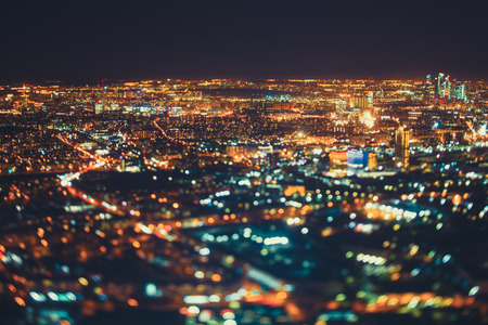 night shift: True tilt shift shooting of residential district in night metropolis from very high point: multiple residential houses, teal and orange lights from windows, strong bokeh in foreground