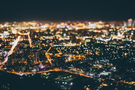 True tilt shift shooting of highway in residential district during night in metropolis from high point: multiple residential houses, road in focus in foreground, strong bokeh in background