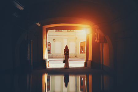 end of a long day: Adult blonde woman in sunglasses and long skirt is standing with bag in the end of long dark tunnel with reflective floor on sunny day with flare, city road and wall of residential house in background