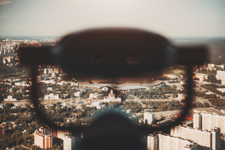 Blurred silhouette of binocular in foreground and summer cityscape in background from very high point, view of Moscow city and VDNKh district on sunny day with many residential buildings and parks Stok Fotoğraf