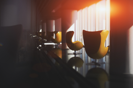 specular: Two empty curved contemporary yellow armchairs standing near each other on reflective floor of modern luxury office interior next to window with mirror behind making a lot of reflections in distance