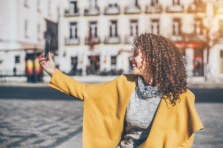 Attractive curly smiling Brazilian woman in yellow coat and sweater having video call using smart phone, adult beautiful laughing lady making selfie on cell phone while standing on sunny street