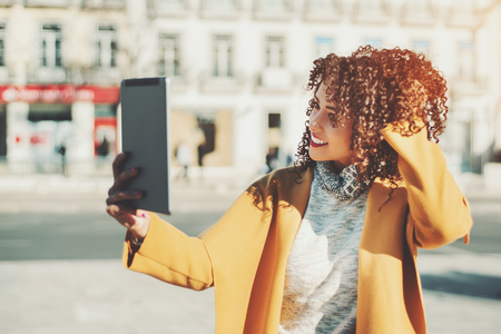 electronic book: Attractive curly Brazilian woman in yellow coat and sweater having video call using digital tablet, adult beautiful smiling lady making selfie on touch pad while standing on city street on sunny day