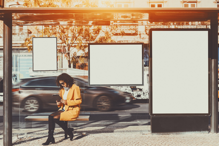 Curly brunette woman in sunglasses and yellow coat working on her digital tablet while sitting and waiting bus inside of glass city bus stop, with several blank mock-up banners around her Zdjęcie Seryjne - 75228606