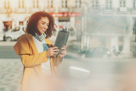 aberrations: Beautiful smiling curly Brazilian woman in yellow coat having video call using digital tablet, adult attractive lady making selfie on touch pad with copy space for your message or promotional content Stock Photo