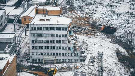 salvaging: View from high point of dismantling and demolition of a multi-storey house in residential district: construction machinery, piles of garbage powdered with snow, heavy machinery around, winter day