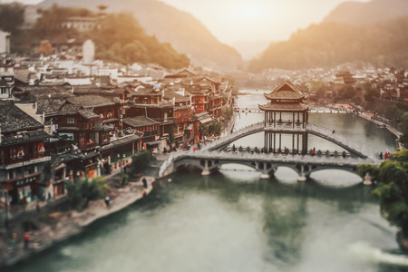True tilt shift view of double decker bridge over the river with pagoda and multiple beautiful residential houses, scenery hazy landscape of Vietnam village placed on hills with river in the middle 版權商用圖片