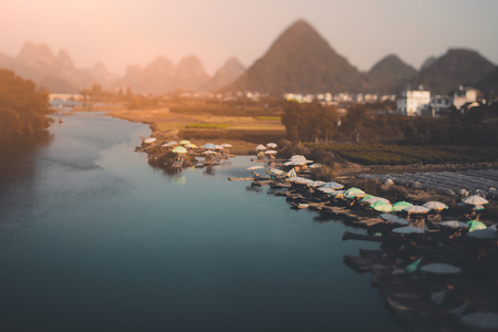 True tilt shift view of small harbor on river in Vietnam surrounded by hills, dramatic tropical landscape with port, water, multiple small rafts and boats, village and bridge in blurred background