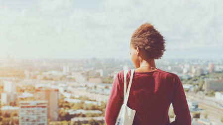 Rear view of young mixed Brazilian teen girl with curly afro hair waving in the wind standing on high point and looking down on city district, sunny summer cityscape below in blurred background