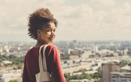 Portrait of young beautiful cute mixed Brazilian teen girl with curly afro hair standing on observation point very high and half-turned to camera, sunny summer cityscape below in blurred background
