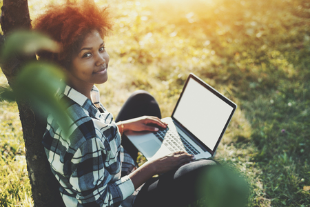 Attractive black teen girl in checkered shirt with laptop sitting on grass of spring meadow on sunny summer day, charming mixed female with curly afro hair and net-book leaning on apple tree in park