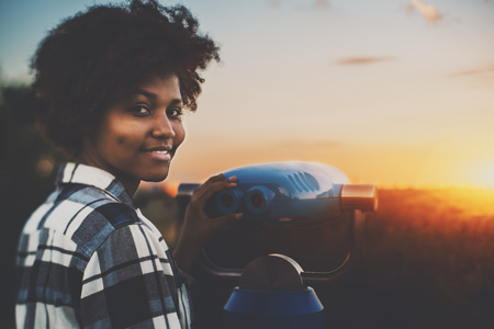 Cute biracial teenage female in plaid shirt is using street telescope to observe evening cityscape, young black girl with curly hair and dimples near blue binocular is preparing to look at sunset Stok Fotoğraf