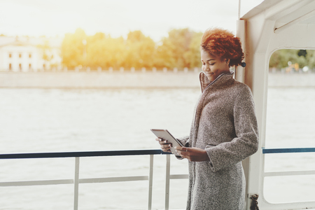 Attractive smiling mixed girl is standing on the deck of a ship with digital tablet, cute black teenage female with curly afro hair holding touch pad while standing on seafront with copy space