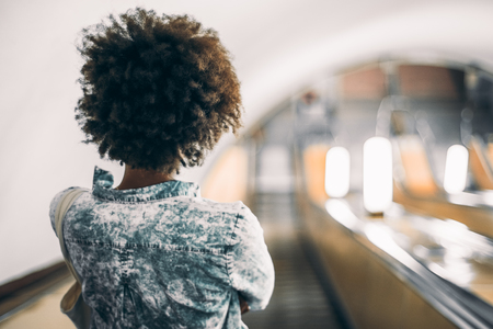 Rear view of black teenage girl with curly afro hair in trendy blue shirt standing on descending escalator in subway with copy space for young advertising text message or promotional content Stock Photo