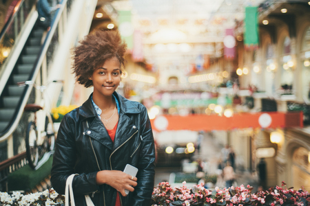 Beautiful black teenage girl in leather jacket and with smart phone is standing in huge multistorey shop, attractive mixed young female with curly afro hair during shopping with copy space for message