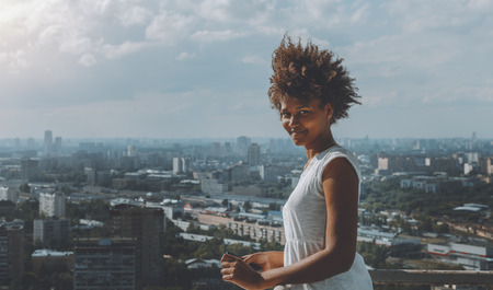 Charming black girl with curly african hair is standing on very high balcony of skyscraper on observation point and looking in camera with copy space area for text message or logo, sunny summer day