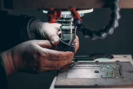 aluminium: View of worker hands while he is changing drilling tool cutter in CNC milling machine during pause of treatment of aluminum blank fixed on moving table in dark settings of workshop room Stock Photo