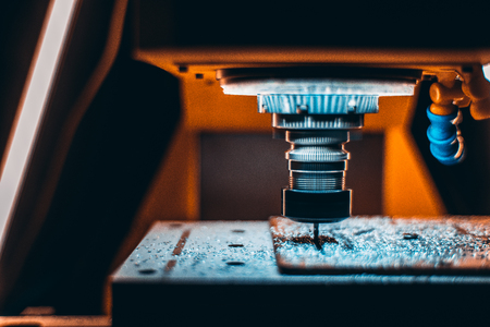 aluminum: Close-up view of work in progress of CNC milling machine with warm blacklight, a lot of metalworking chips around and rotating cutter tool during treatment process with copy space for text