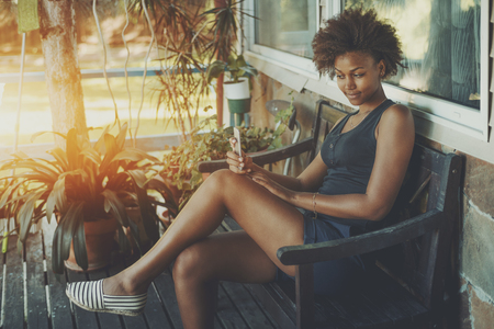 Cute brazilian lady is sitting on the veranda of tropical summer house and making selfie on her smart phone, young curly afro american girl spending her morning on black bench of private cottage Stock Photo