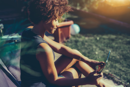 Side view of young sexy afro american girl sitting in park bench and talking with her boyfriend via digital tablet, curly mixed teenage female is reading electronic book in sunny summer garden