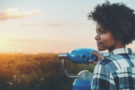 Tilt-shift portrait of meditative young black female with afro curly hair standing in high observation point and holding blue binocular with copy space zone for text, logo or your advertising, sunset Stok Fotoğraf - 79556057
