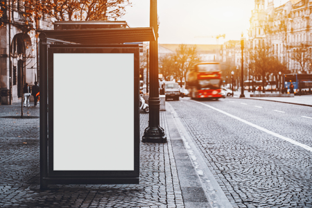 White empty information mock-up on city bus stop, blank vertical billboard near paved road with red touristic bus, clear placeholder frame in urban settings with copy space for text or advertising Imagens - 79665275