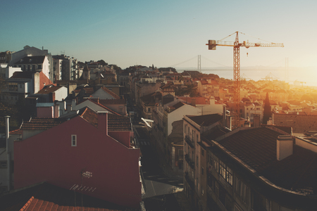 View of morning sunny narrow street in central district of Lisbon in Portugal with teal sky, small ancient houses with beautiful facades, construction cranes, huge famous rope bridge and hazy horizon Banco de Imagens