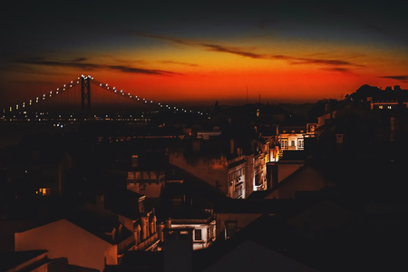 View from hight point of illuminated narrow street with beautiful old facades of residential houses, following to rope bridge during stunning red and orange sunset in Lisbon, Portugal