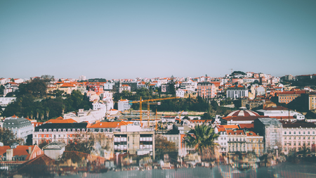 Aerial panoramic shooting from observation point of central Lisbon district on sunny day: multiple ancient houses, plants, construction cranes, clear sky and reflections with aberrations in the bottom Banco de Imagens