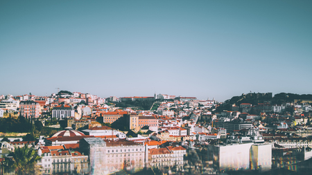 Wide beautiful panoramic view from high point of central  Lisbon district on sunny summer day: multiple houses with red roofs, castle in distance, clear sky and reflections with aberrations in bottom