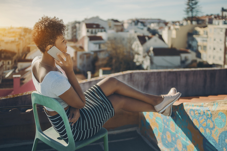 Charming afro american lady sitting on teal chair on roof of Lisbon residential house and talking via smart phone, young Brazilian girl having rest on balcony of European city and phoning with friend