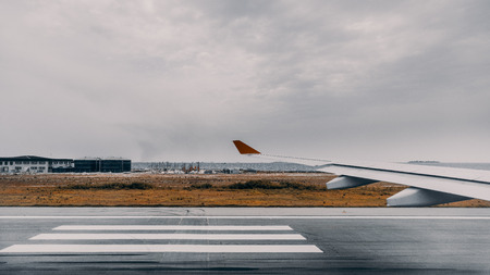Wide angle view from aircraft window of take-off runway with stripes of zebra, airplane wing, dry grass and infrastructure of Male international airport, overcast sky, Indian ocean in background