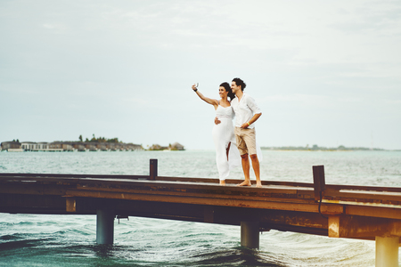 Beautiful newly married couple making selfie using modern smartphone on Maldives resort during their honeymoon while standing on bridge, with copy space zone for logo, text or advertising message Stock Photo