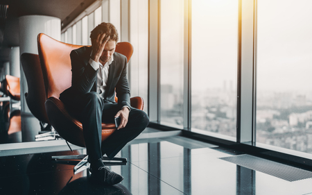 Businessman in formal suit is sitting on orange armchair and holding his head in depression after phone call about his company went bankrupt with copy space for text, your logo or advertising message Stock fotó