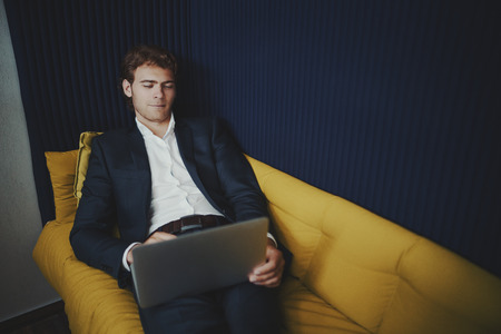 chillout: Handsome businessman with short beard is leaning on yellow sofa in office chillout zone and having video conversation with his family during lunch time at his work Stock Photo