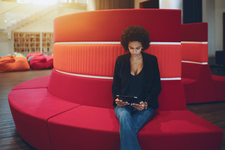 chillout: Young serious afro american girl with curly hair is sitting on red curved sofa in chillout office space and reading e-mail from her boss about future meeting with copy space place for text or logo Stock Photo