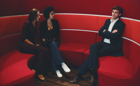 chillout: Two businesswomen (caucasian and black with curly afro hair) looking angry on their male colleague in business suit because he came to their sofa in office chillout during their private conversation