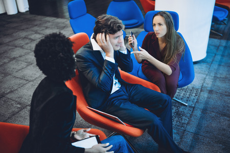 argumentation: Two female business colleagues blaming their male co-worker while they three together having quarrel in office, businessman sitting in central armchair is very stressed and closing his ears with hands