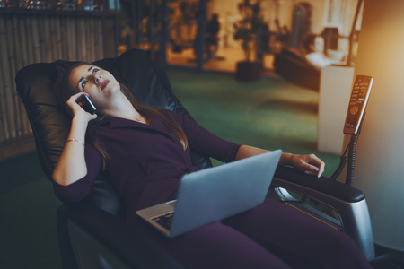 chillout: Beautiful caucasian businesswoman is chilling on modern leather massage chair, laying relaxed with laptop on her knees and having conversation with her family during lunch time in office chillout