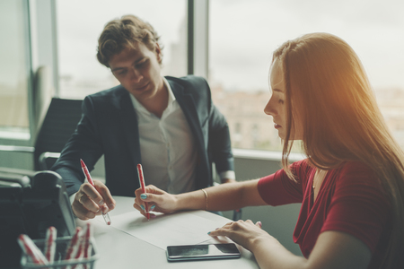 occiput: Attractive man entrepreneur having work conversation with his female beautiful co-worker, businesswoman explaining her colleague  new development strategy using sheet of paper and pen during meeting